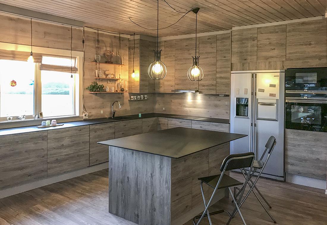 Kjøkkenøy bygd opp av tre skapseksjoner og tre skuffeseksjoner. Utførelse i Oslo-Eik med drivved effekt. Benkeplate i 12 mm kompaktlaminat med nydelig svart matt overflate, som ikke viser fingermerker, og samtidig er bakterieresistent (Fenix nanolaminat).