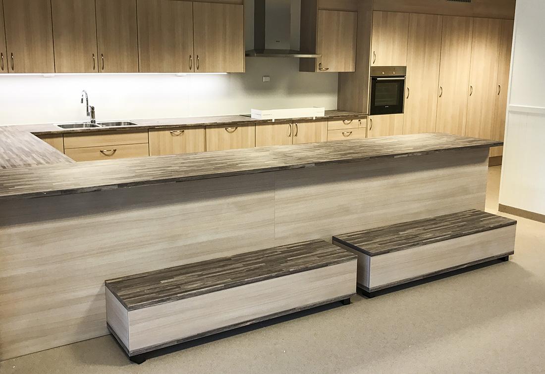 """Kjøkken produsert i lys eik med """"malavibrun"""" benkeplate"""